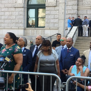 Emerald Garner, daughter of Eric Garner, speaks at a press conference Tuesday after an announcement that the U.S. Attorney's Office for the Eastern District of New York will not file federal charges against police officers who killed Garner in 2014. The Rev. Al Sharpton and Garner's mother, Gwen Carr, are pictured in the second row. (Photo by AMANDA OTTAWAY/Courthouse News Service)