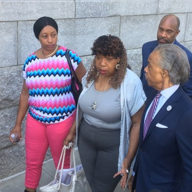 Eric Garner's mother Gwen Carr (center) leaves a press conference Tuesday after an announcement that the U.S. Attorney's Office for the Eastern District of New York will not file federal charges against police officers who killed Garner in 2014. The Rev. Al Sharpton is at Carr's left. (Photo by AMANDA OTTAWAY/Courthouse News Service)