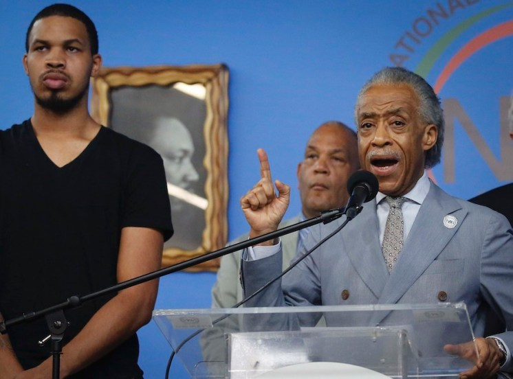 Eric Garner Jr., left, the son of chokehold victim Eric Garner, listens as Rev. Al Sharpton, right, founder of the National Action Network, speaks during a August 20, 2019, press conference after NYPD Commissioner James O'Neill announced his decision Monday to fire NYPD officer Daniel Pantaleo for the 2014 chokehold death of Eric Garner, at NAN headquarters in New York. (AP Photo/Bebeto Matthews)