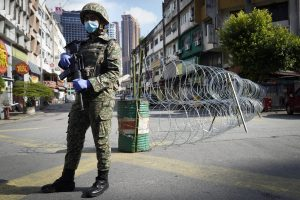 A soldier wearing a face mask stands guard near barbed wire in a locked down area due to the new coronavirus in Kuala Lumpur, Malaysia, Friday, May 15, 2020. Despite a sharp drop in infections, Malaysia's leader said restrictions to fight the coronavirus will be extended by four more weeks until June 9. The government has already let most businesses reopen with strict conditions to help revive a hard-hit economy. But mass gatherings are still barred, with schools, cinemas and houses of worship staying shut, group sports prohibited and interstate travel banned. (AP Photo/Vincent Thian)