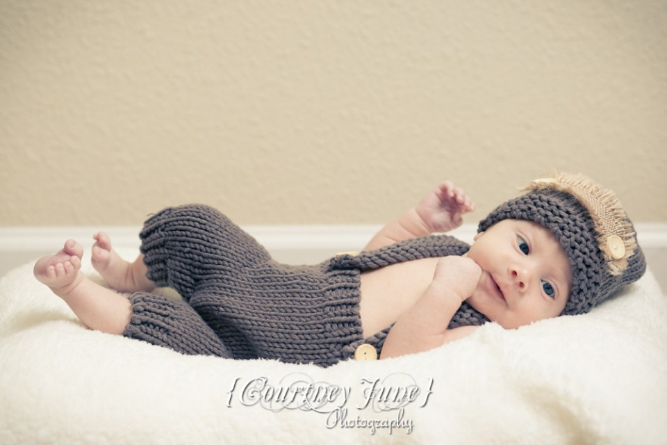 newborn photographer photographing a newborn in a brown knit jumper laying on his back smiling