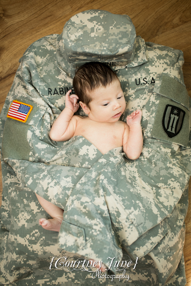 newborn photographer photographing a newborn laying on daddy's army jacket