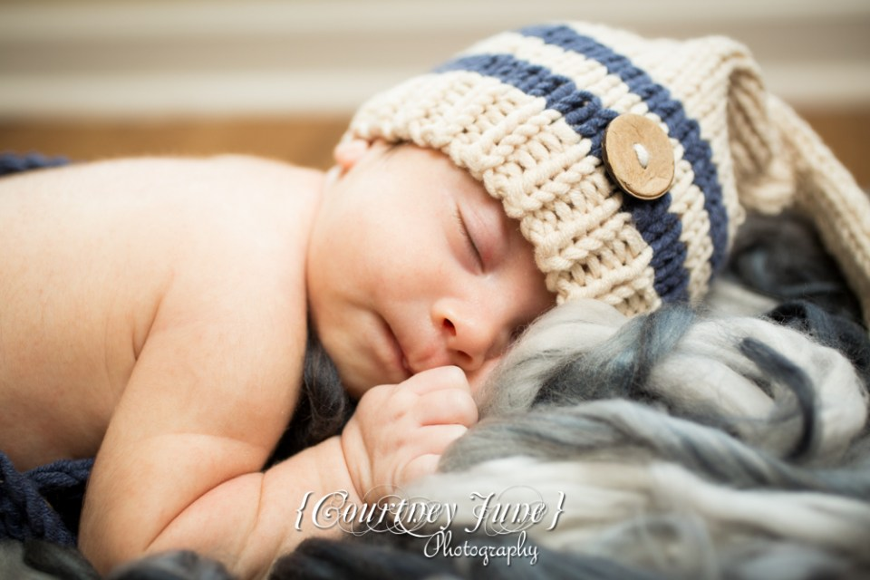 newborn photographer photographing a closeup of a newborn with a knit hat on