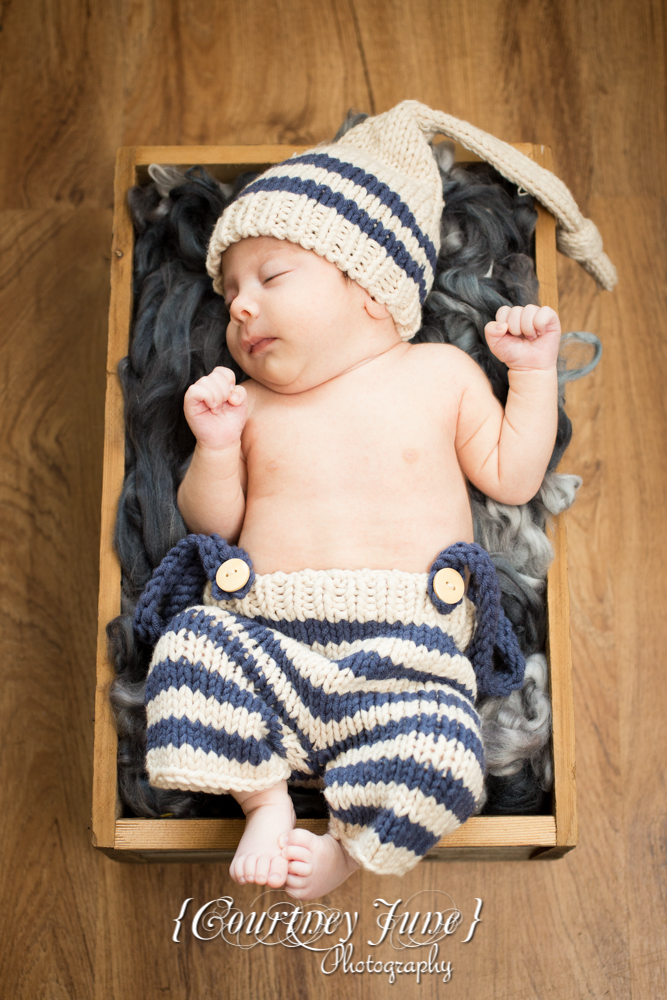 newborn photographer photographing a newborn in a wooden crate with a knit outfit and knit hat