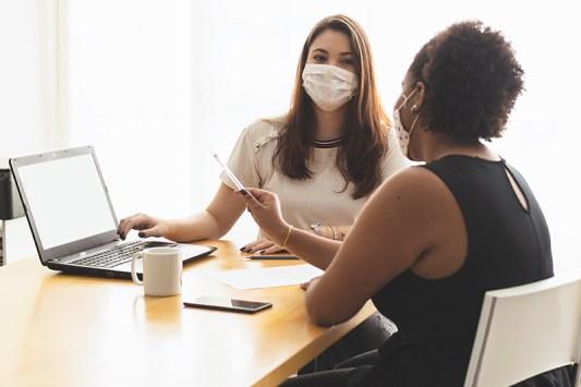 two women wearing masks meeting