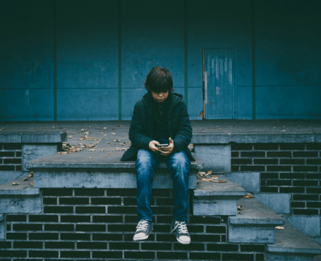 young boy sitting on stairs alone on cell phone