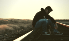 young man sitting on train tracks thinking