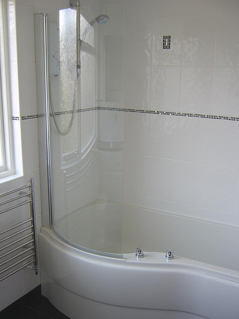 P Shape shower bath with white tiles and black and silver