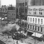 Photograph of the 1914 fire at John B. Varick Hardward Co. on Elm Street in Manchester, NH. Firemen are pictured with a steam fire engine extinguishing the fire. Manchester Historical Association Photoprint Collection.