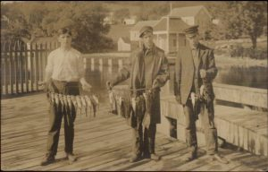 Old postcard of Meredith New Hampshire's dock and fishing trophies. The bait must have been good.