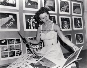 1950's photograph of Ilene Woods reviewing Disney sketches.