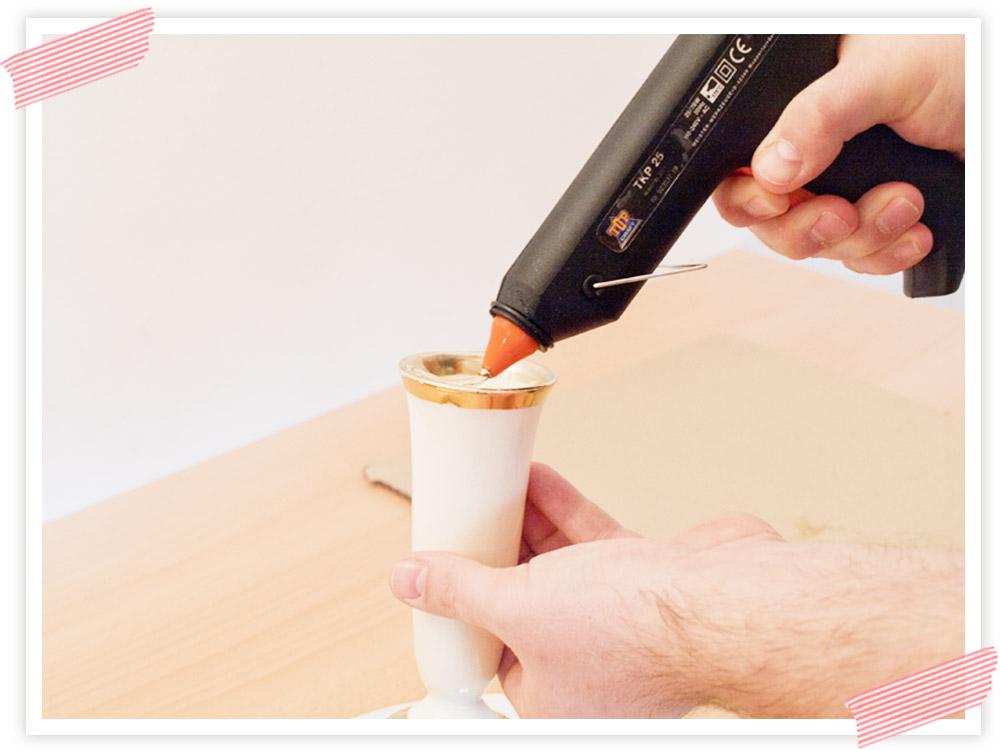 Zuerst den Klebstoff auf den oberen Rand der Vase auftragen. Dabei aufpassen, dass nicht so viel Klebstoff über den Rand quillt.