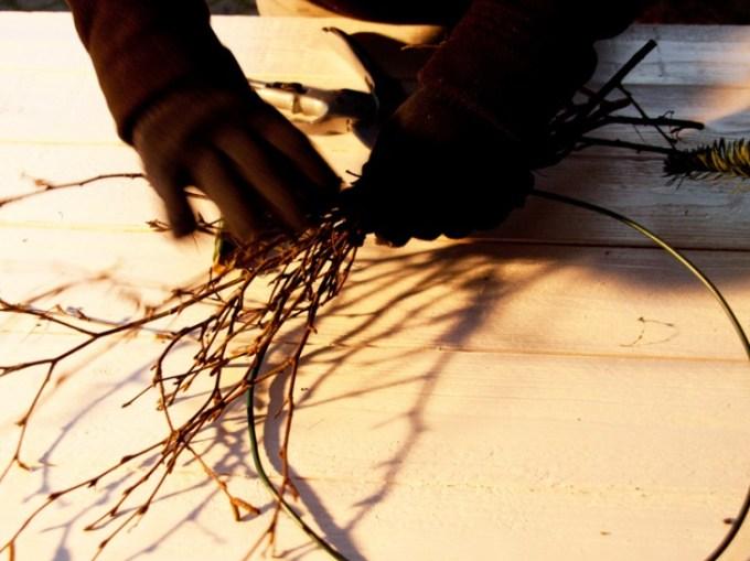 Kleine Büschel aus Zweigen zusammenfassen, die unteren Enden glatt mit der Gartenschere abschneiden und um den Drahtring legen.