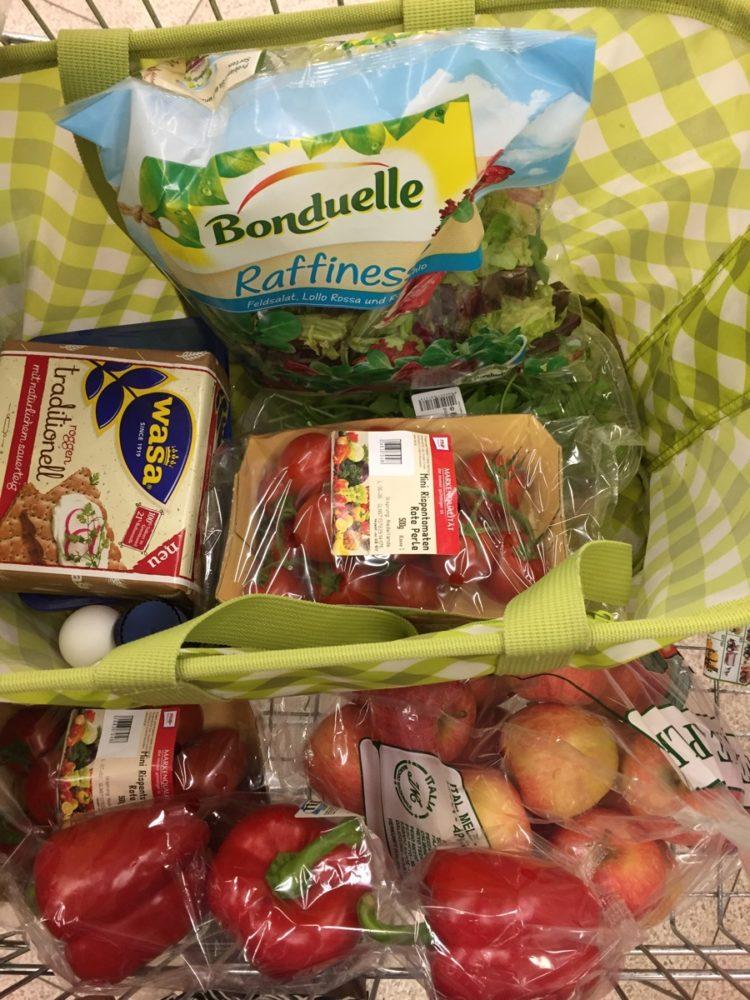 Um eine Menge Gemüse in Plastik in den Einkaufswagen zu werfen