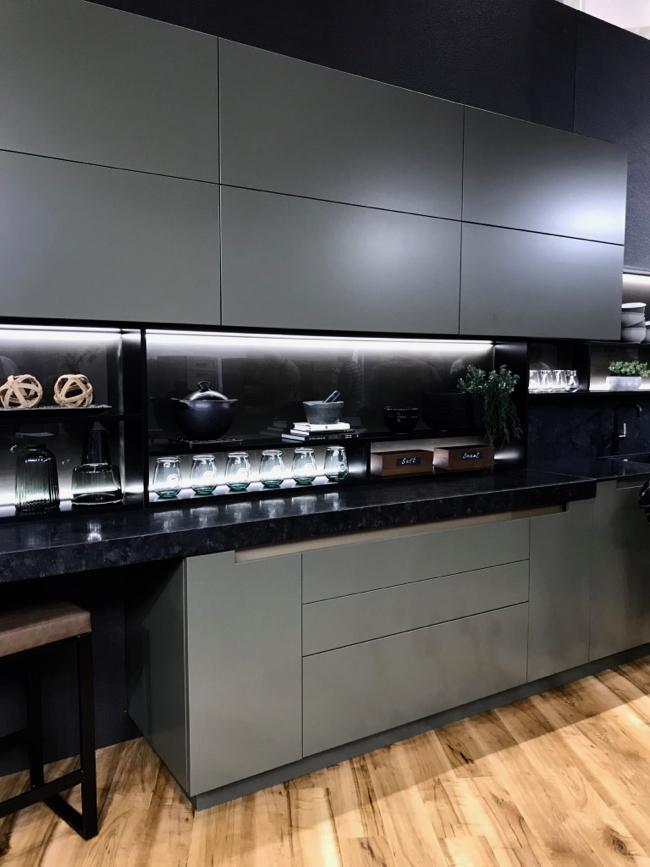 Matte gunmetal and black countertop and backsplash with accent lighting by Cabico