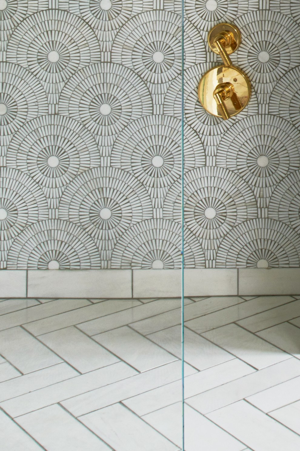 Bianco dolomiti mosaic and herringbone tile with brass plumbing