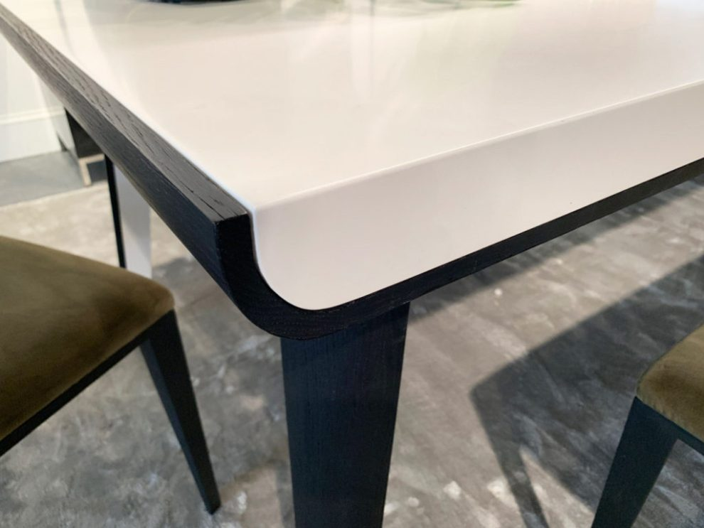 white Rounded Rectangular dining table with dark wood trim Spring 2019 Design Trends - High Point Market