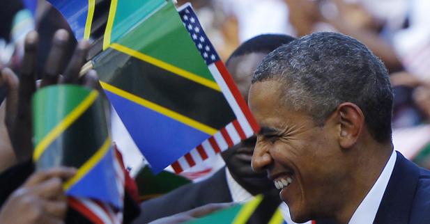 U.S. President Barack Obama is surrounded by Tanzanian and United States flags while greeting people at an official arrival ceremony in Dar Es Salaam