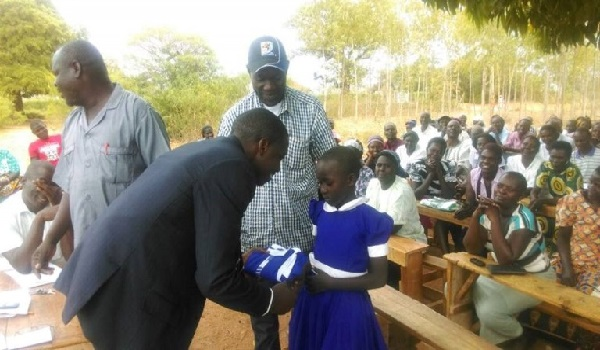 Officials of Africa giving the girls some school unforms. Image Credit: Anike Africa Foundation