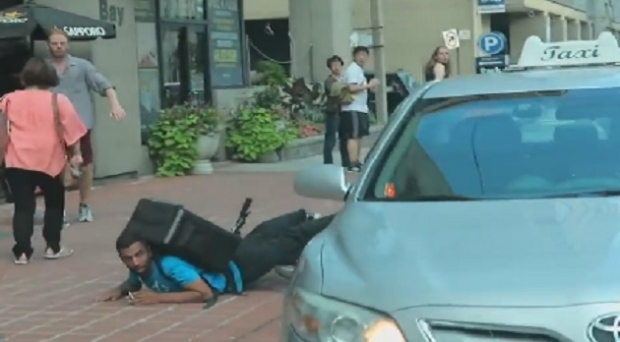 This still image taken from a video posted online shows a bike courier lying on the sidewalk after being struck by a taxi in downtown Toronto.