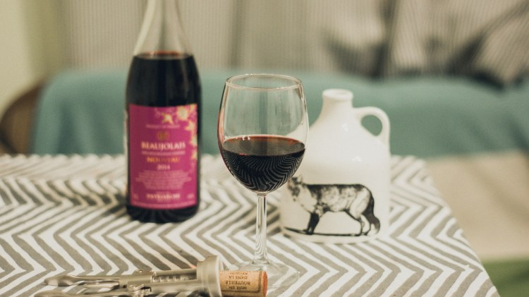 a glass of beaujolais red wine and bottle