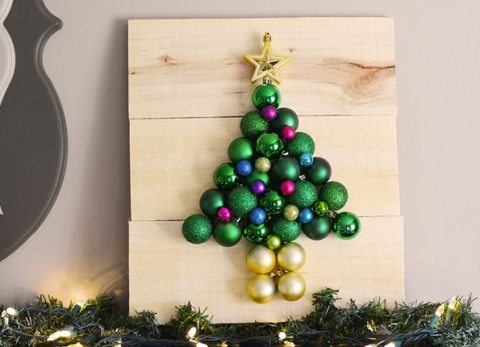 Grab some inexpensive plastic ornaments and a few pallet boards and you can make this pallet Christmas tree that is guaranteed to never drop needles!