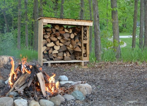 Make your own firewood storage using pallets to keep wood dry for your next family bonfire!