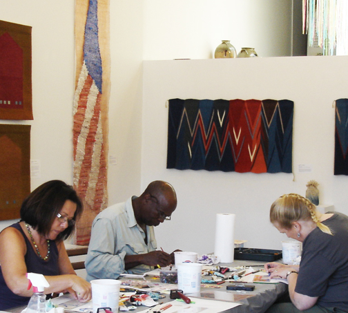 Attendees, unapologetic, crafted their own money-themed monotypes while an American flag stood watching (a weaving by Consuelo Jimenez Underwood) and a printing press stood nearby.