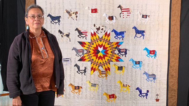 Susan Hudson standing in front of 29 Warriors, quilts