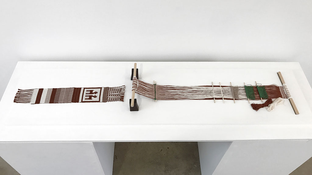 """Jennifer Moore, Backstrap loom and double-weave sampler, 2013, cotton, double-weave pickup. Albers dedicated her seminal text, On Weaving, """"to my great teachers, the weavers of ancient Peru."""" After conquest by the Spanish, some ancient Peruvian weaving techniques, including double-weave, fell into disuse. Nilda Callanaupa, the founder and director of the Center for Traditional Textiles of Cusco, invited Moore to teach double-weave pick-up techniques to members of several Quechua weaving communities at a conference held in Cusco in 2013. This is an example of the looms used and the sampler each weaver made at the conference."""