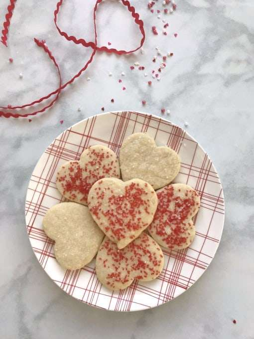 6 Perfect Valentines Heart Shortbread Cookies on a red and white plaid plate with a red rick rack ribbon, with red and white sprinkels