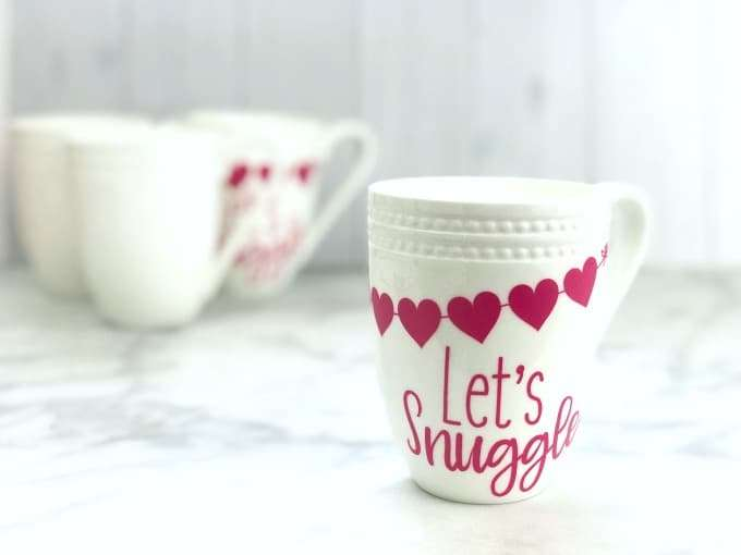 Fun Valentines Party Ideas White coffee mugs with pink hearts and let's snuggle with 3 white mugs in the background