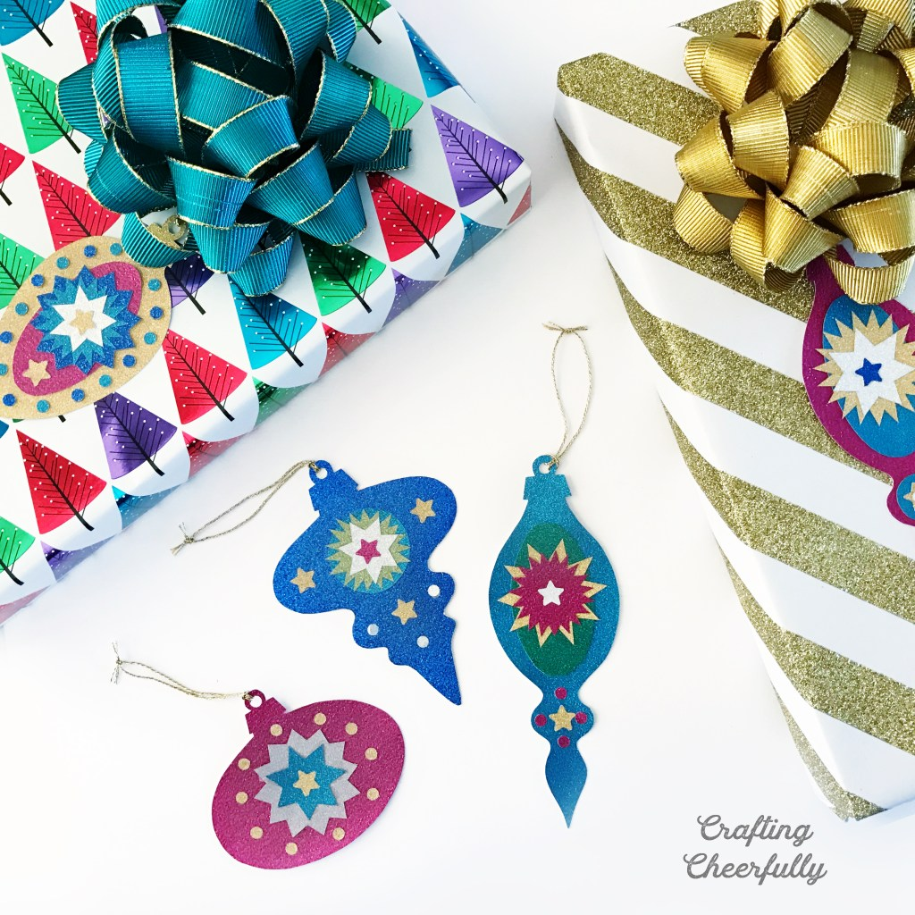 Vintage ornaments in sparkly jewel tone paper lay next to gifts wrapped in gold and sparkly wrapping paper.
