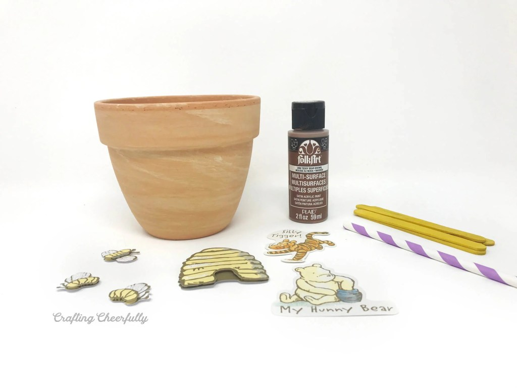 Terra cotta pot, brown acrylic paint and Winnie the Pooh stickers on a white table.