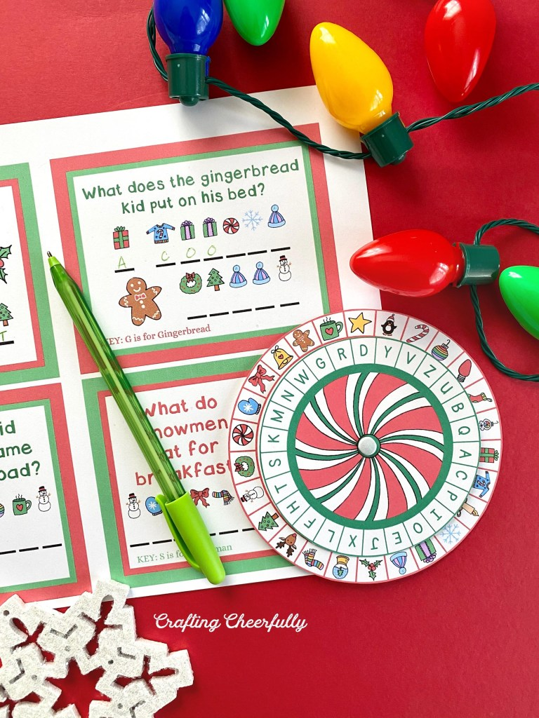 A close up picture of the secret decoder printables laying on a red table. A strand of holiday lights lay near it along with a green pen.