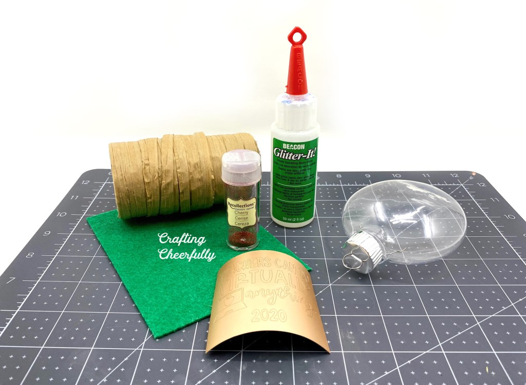Supplies needed for glitter ornament craft sitting on a black self healing mat.