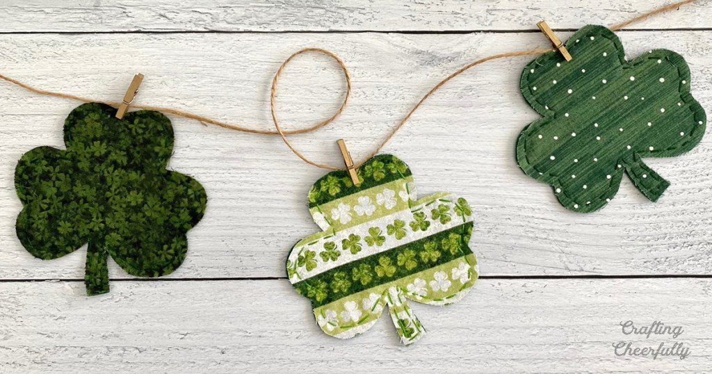 Three fabric shamrocks are clipped to a piece of twine with mini clothespins.