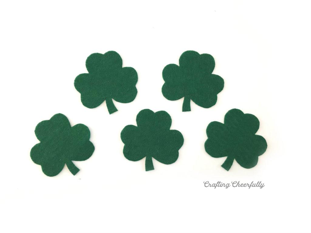 Five green felt shamrocks lay on the white table.