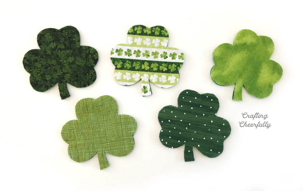 Five fabric shamrocks lay on a white table. The fabric layer is on top of the felt layer.