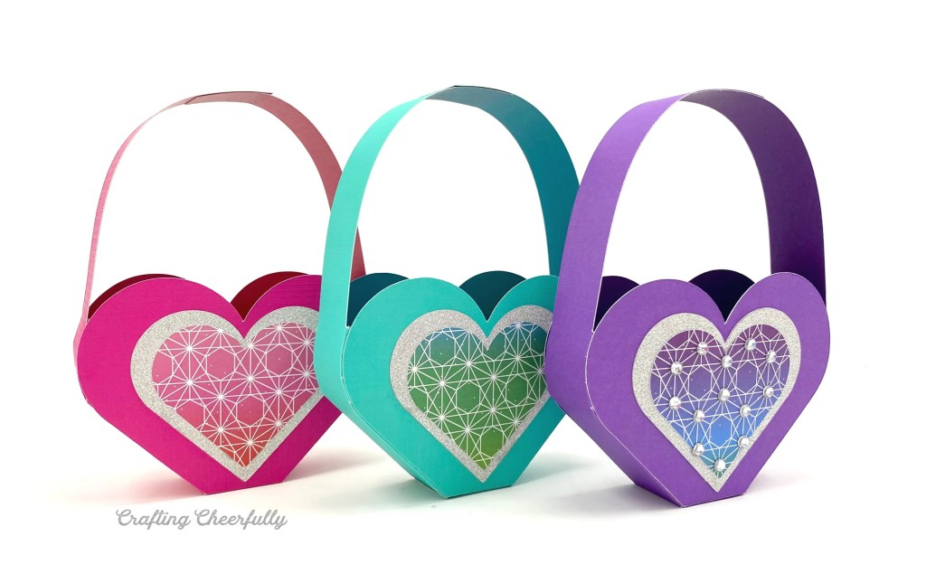 Three heart shaped Valentine boxes sit in a row on a white table. Two roses are next to them.