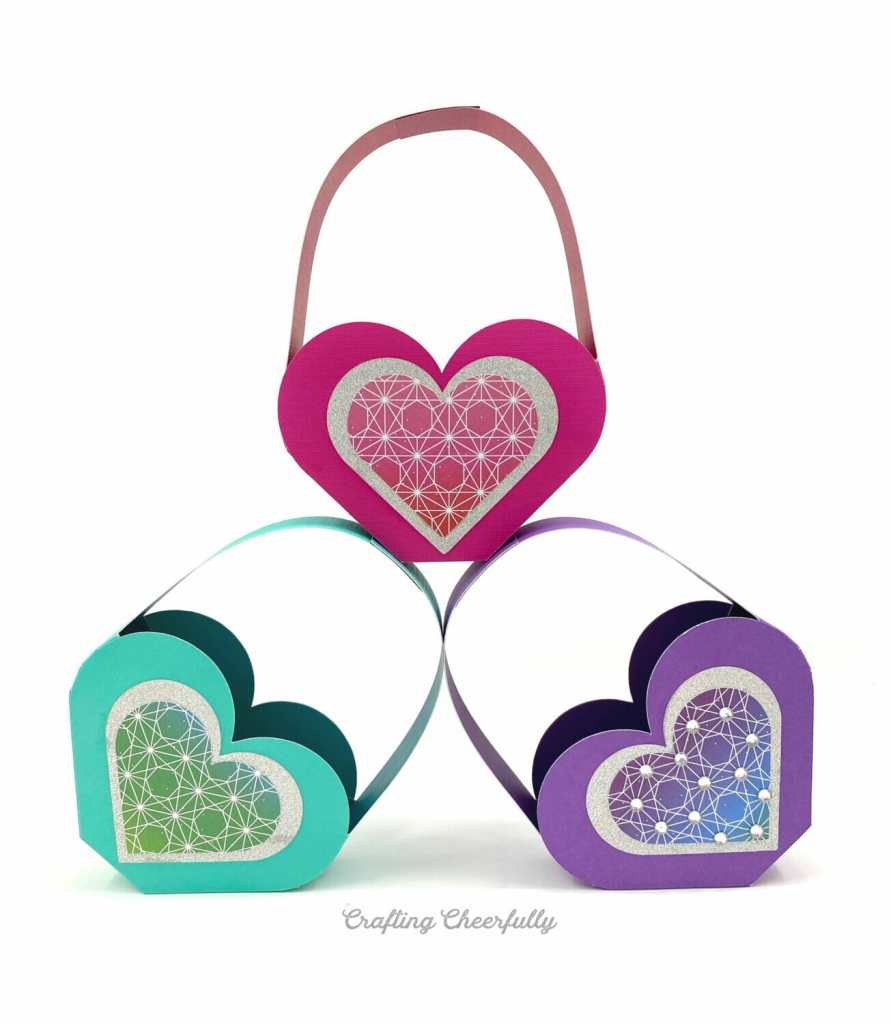 Three heart shaped Valentine boxes sit on a white table stacked on top of each other. They are purple, teal and pink.