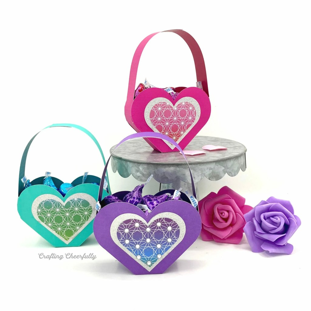 Three heart shaped Valentine boxes filled with candy sit on a white table. Two roses are next to them.