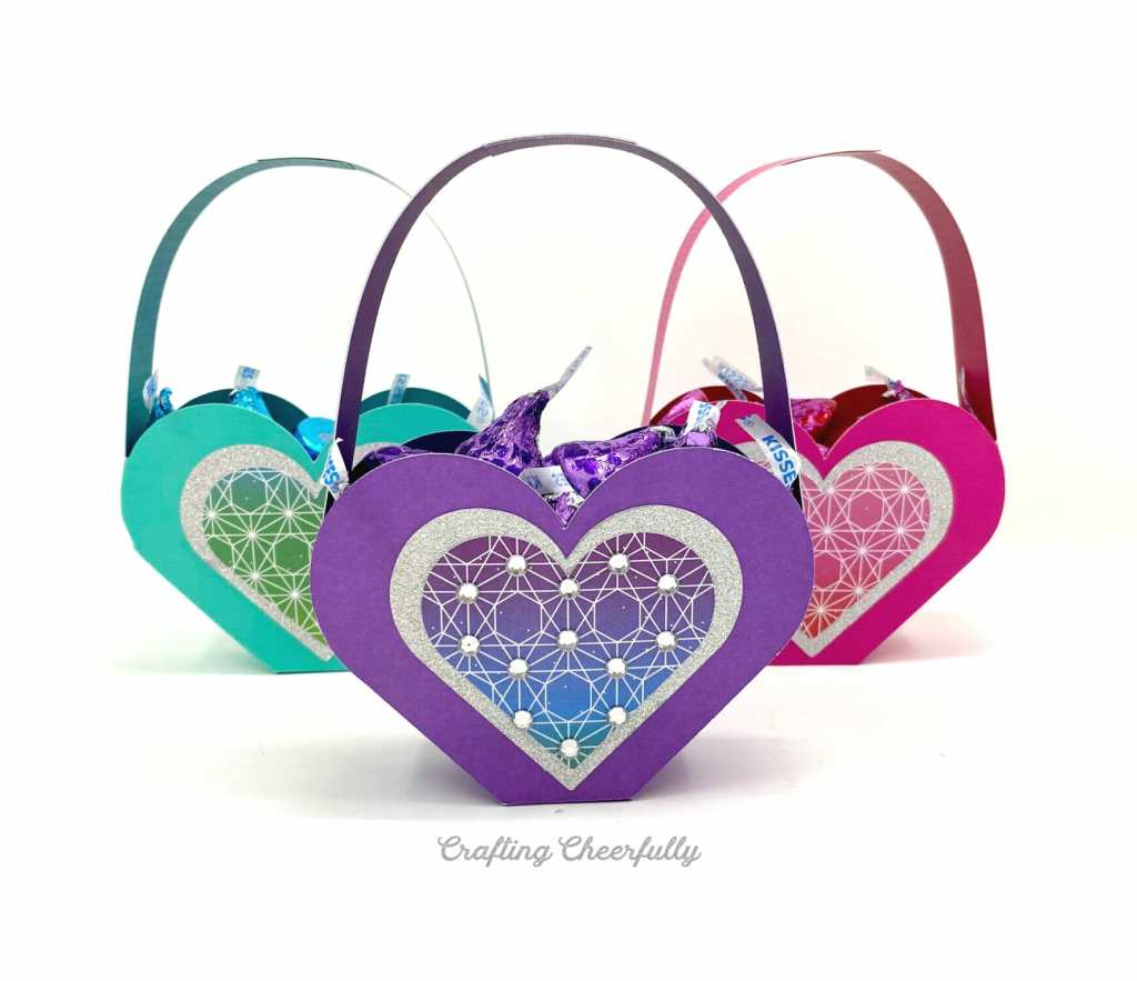 Three heart shaped Valentine boxes filled with candy sit on a white table. They are purple, teal and pink.