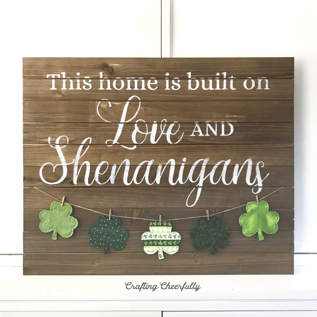 """Wooden sign with the words """"This home is built on Love and Shenanigans"""" with a banner of fabric shamrocks hanging on the bottom."""