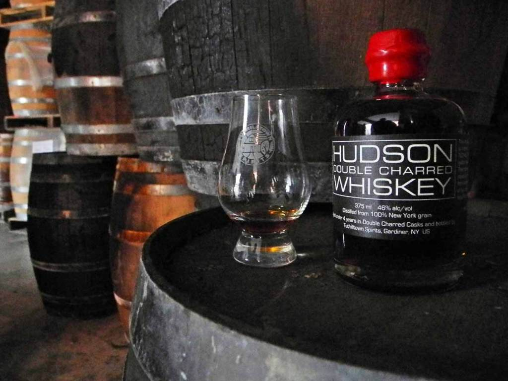 a bottle of Hudson Double Charred Whiskey sitting on top of a whiskey barrel.
