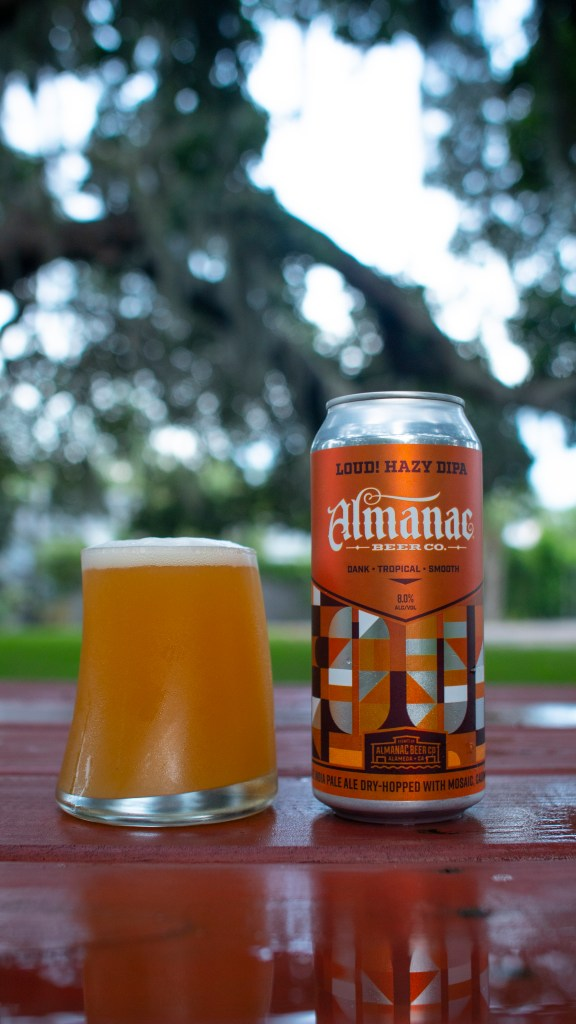 A beer can of LOUD! Hazy DIPA and a glass of poured beer sitting on a picnic table.