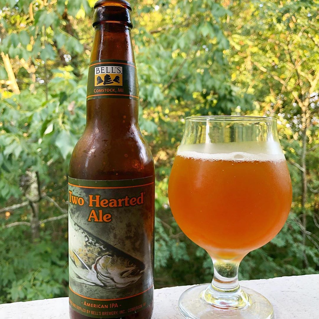 Two hearted Ale poured into a glass which is located outside in nature
