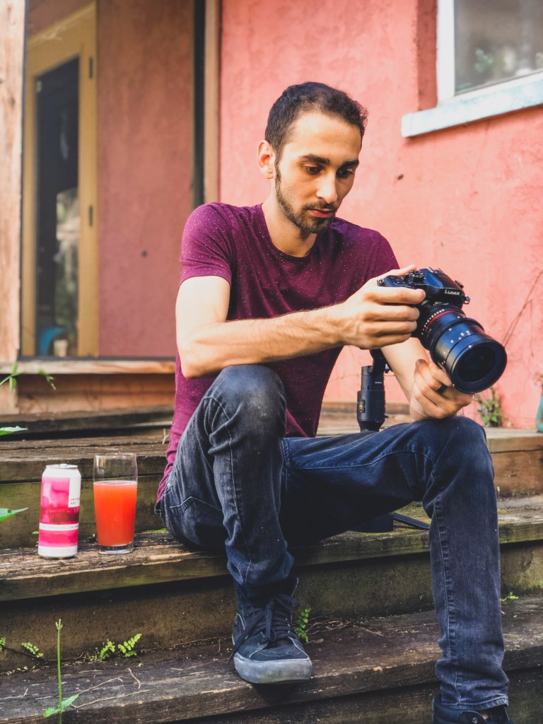 A man (James Bixby) looking at his camera to review the footage and photos. Next to him is a glass full of beer (Pink Lemonade IPA by Untitled Art Brewing).