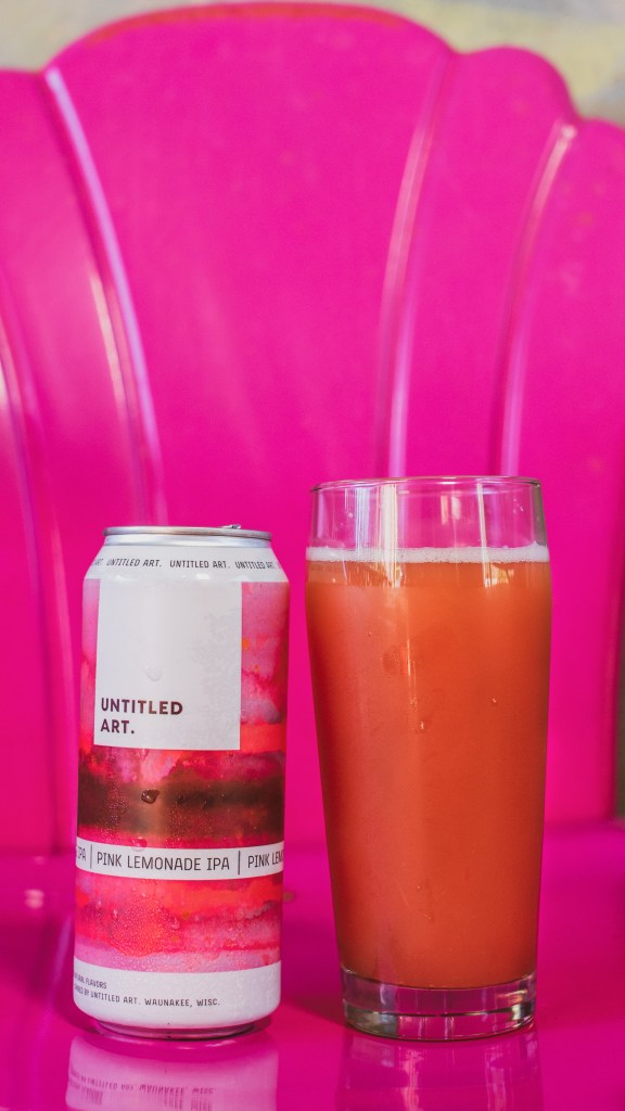 A can of beer on a vintage pink lawn chair. The beer color is a similar reddish hue. Pink Lemonade IPA by Untitled Art Brewing).
