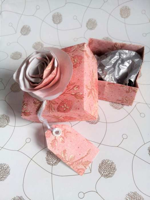 handmade pink paper box with the lid off with silver tissue filling and a paper tag